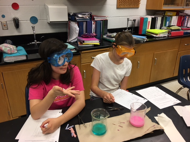 image: science students completing an experiment
