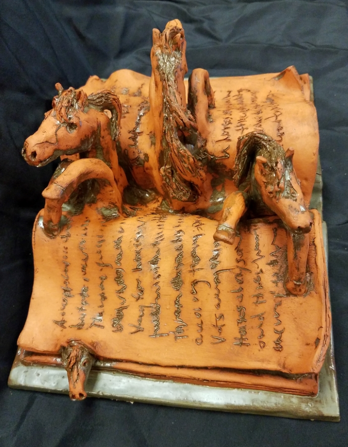 image:  three horses emerging from pages of book